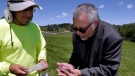 In this June 14, 2018 photo, Wade Lawrence, right, museum director and senior curator at The Museum at Bethel Woods, looks at artifacts recovered from a dig at the site of the original Woodstock Music and Art Fair, in Bethel, N.Y. (AP Photo/Richard Drew)