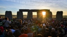 The sun rises through the stones at Stonehenge as crowds of people gather to celebrate the dawn of the longest day in the U.K., in Wiltshire, England, Thursday June 21, 2018. (Ben Birchall/PA via AP)