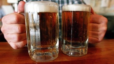 A bartender serves two mugs of beer at a tavern in Montpelier, Vt. THE CANADIAN PRESS/AP/Toby Talbot