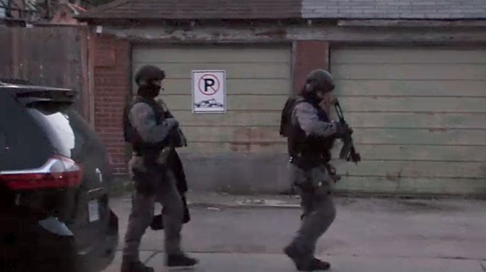 Tactical officers conduct a raid in Toronto as part of a targeted investigation into alleged criminal organization on June 21, 2018.