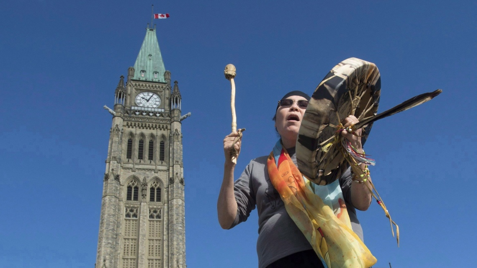 Chief Marcia Brown Martel sings outside the parliament buildings following a government news conference announcing a compensation package for indigenous victims of the sixties scoop, in Ottawa on Friday, October 6, 2017. THE CANADIAN PRESS/Adrian Wyld