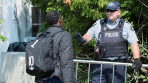 An asylum seeker, claiming to be from Eritrea, is questioned by an RCMP officer as he crosses the border into Canada from the United States Monday, August 21, 2017 near Champlain, N.Y. (THE CANADIAN PRESS/Paul Chiasson)