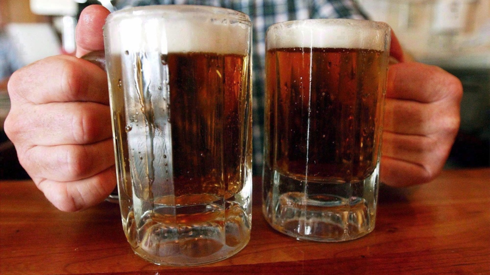 A bartender serves two mugs of beer at a tavern in this file photo.