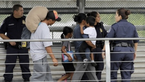 Ever Castillo, left, and his family, immigrants from Honduras, are escorted back across the border by U.S. Customs and Border Patrol agents in Hildalgo, Texas on Thursday, June 21, 2018. (AP Photo/David J. Phillip)