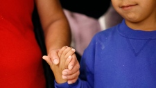 Darwin Micheal Mejia, right, holds hands with his mother, Beata Mariana de Jesus Mejia-Mejia, during a news conference following their reunion at Baltimore-Washington International Thurgood Marshall Airport, Friday, June 22, 2018, in Linthicum, Md. The Justice Department agreed to release Mejia-Mejia's son after she sued the U.S. government in order to be reunited following their separation at the U.S. border. She has filed for political asylum in the U.S. following a trek from Guatemala. (AP Photo/Patrick Semansky)