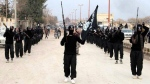 This undated file image posted on a militant website on Tuesday, Jan. 14, 2014, which has been verified and is consistent with other AP reporting, shows fighters from the Islamic State group marching in Raqqa, Syria. (AP Photo/Militant Website)