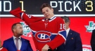 Jesperi Kotkaniemi, of Finland, dons a Montreal Canadiens jersey after being chosen by the team during the NHL hockey draft in Dallas, Friday, June 22, 2018. (AP Photo/Michael Ainsworth)