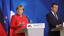 German Chancellor Angela Merkel, left, and French President Emmanuel Macron address the media at an EU summit in Brussels on Friday, June 23, 2017. European Union leaders met in Brussels on the final day of their two-day summit to focus on ways to stop migrants crossing the Mediterranean and how to uphold free trade while preventing dumping on Europe's markets. (AP Photo/Olivier Matthys)
