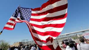 "In this June 21, 2018 file photo, protesters and media gather outside a closed gate at the Port of Entry facility, where tent shelters are being used to house separated family members in Fabens, Texas. The tumult of the past week along the southern border crystalized how the GOP has shifted from the ""compassionate"" conservatism George W. Bush articulated to win the presidency twice, buoyed by the support of 44 percent of Latinos in 2004. Instead, wrenching photos and audio of the U.S. government separating migrant children from their parents symbolize the tense relationship between Latinos and the White House in the Trump era. (AP Photo/Matt York, File)"