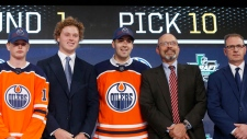 Evan Bouchard, centre, of Canada, poses after being selected by the Edmonton Oilers during the NHL hockey draft in Dallas, Friday, June 22, 2018. (AP Photo/Michael Ainsworth)
