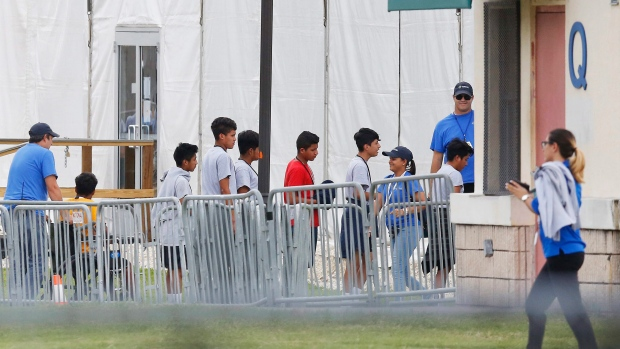 Immigrant children walk in a line outside the Homestead Temporary Shelter for Unaccompanied Children a former Job Corps site that now houses them, on Wednesday, June 20, 2018, in Homestead, Fla. (AP Photo / Brynn Anderson)