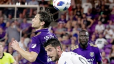 Orlando City's Jonathan Spector, front left, tries to head the ball for a shot on goal over Montreal Impact's Alejandro Silva (9) during the first half of an MLS soccer match, Saturday, June 23, 2018, in Orlando, Fla. (AP Photo/John Raoux)