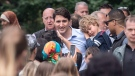 Prime Minister Justin Trudeau greets members of the public as his son Hadrien rests on his shoulder during a visit to a traditional Quebecois village in Drummondville, Que., Saturday, June 23, 2018. (THE CANADIAN PRESS/Graham Hughes)