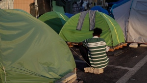 An asylum seeker sits in a camp set by the Baobab aid group, in Rome, Tuesday, June 19, 2018. (AP Photo/Alessandra Tarantino)