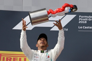Mercedes driver Lewis Hamilton of Britain throws the trophy in the air after winning the French Formula One Grand Prix at the Paul Ricard racetrack, in Le Castellet, southern France, Sunday, June 24, 2018. (AP Photo/Claude Paris)