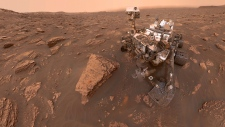 This composite image made from a series of June 15, 2018 photos shows a self-portrait of NASA's Curiosity Mars rover in the Gale Crater. The rover's arm which held the camera was positioned out of each of the dozens of shots which make up the mosaic. A dust storm has reduced sunlight and visibility at the rover's location. (NASA / JPL-Caltech via AP)