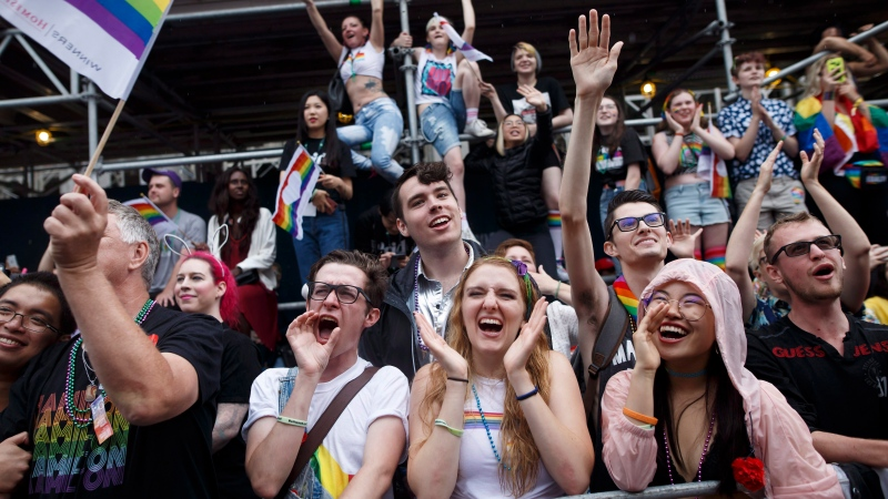 Revellers cheer from the sidewalk as they watch the Toronto Pride parade on Sunday, June 24, 2018 in Toronto. THE CANADIAN PRESS/Cole Burston
