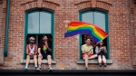 Revellers watch from apartment windows above the parade route during the Toronto Pride parade on Sunday, June 24, 2018 in Toronto. THE CANADIAN PRESS/Cole Burston