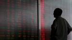 A man looks at an electronic board displaying stock prices at a brokerage house in Beijing, Monday, June 25, 2018. (AP Photo/Andy Wong)