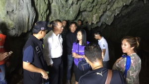 In this Saturday, June 23, 2018, photo, the Governor of Chiang Rai Narongsak Osatanakorn talk to his staff in the entrance of the cave where a group of boys went missing in Chiang Rai, Thailand.  (Chiang Rai City Public Affairs Department via AP)