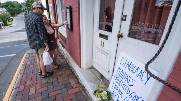 Passersby examine the menu at the Red Hen Restaurant Saturday, June 23, 2018, in Lexington, Va. (AP Photo/Daniel Lin)/Daily News-Record via AP)