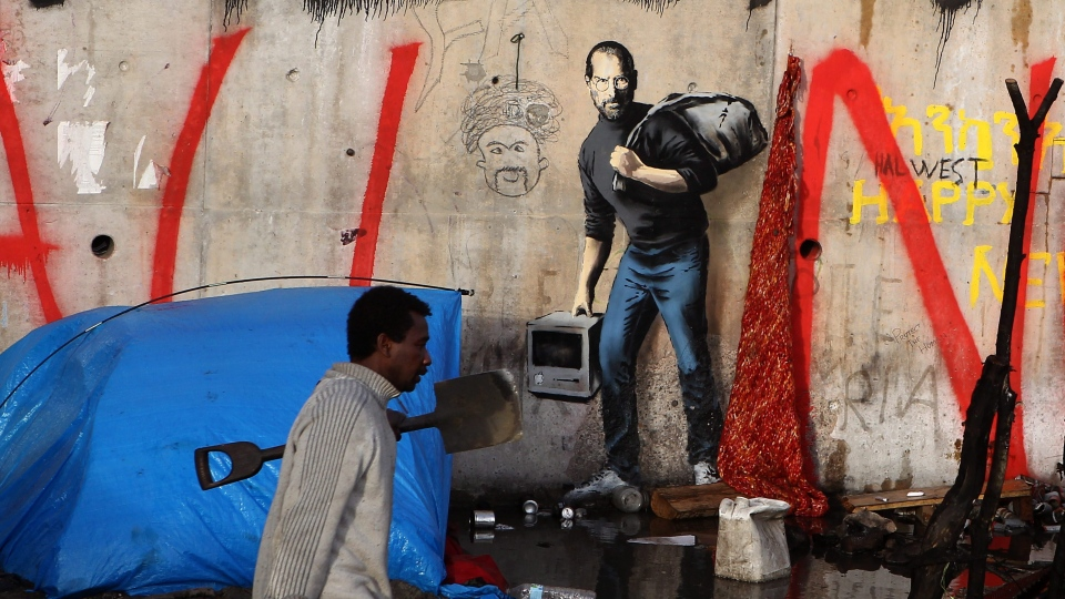 A migrant walks past a painting by English graffiti artist Banksy, at the entrance of the Calais refugee camp in France, in Calais, northern France, Monday, Dec. 21, 2015. The elusive graffiti artist has depicted the late Apple guru Steve Jobs — whose biological father was from Syria — carrying a black garbage bag and an early model of the Macintosh computer. (AP Photo/Michel Spingler)