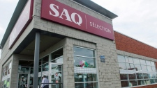 A man leaves an SAQ outlet on Monday, June 18, 2018 in Montreal. THE CANADIAN PRESS/Ryan Remiorz