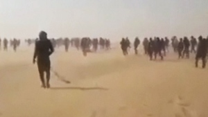 Migrants are seen walking through the Sahara on their way to Niger in this still image taken from video. (Credit: Mohammed Bah)