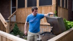 Mike Potwin, who co-shares a cottage with his brother's family, makes dinner on his BBQ in his backyard in Toronto, Monday, June 18, 2018. THE CANADIAN PRESS/Marta Iwanek