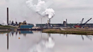 The Syncrude oil sands extraction facility is reflected in a tailings pond near the city of Fort McMurray, Alberta on Sunday June 1, 2014. (THE CANADIAN PRESS/Jason Franson)
