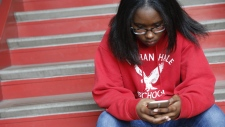 Ayrial Miller, 13, checks her phone