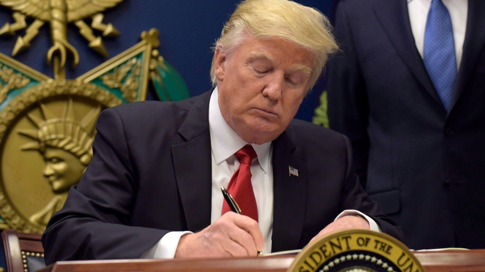 U.S. President Donald Trump signs an executive order on extreme vetting during an event at the Pentagon in Washington on Jan. 27, 2017. (THE CANADIAN PRESS/AP, Susan Walsh)
