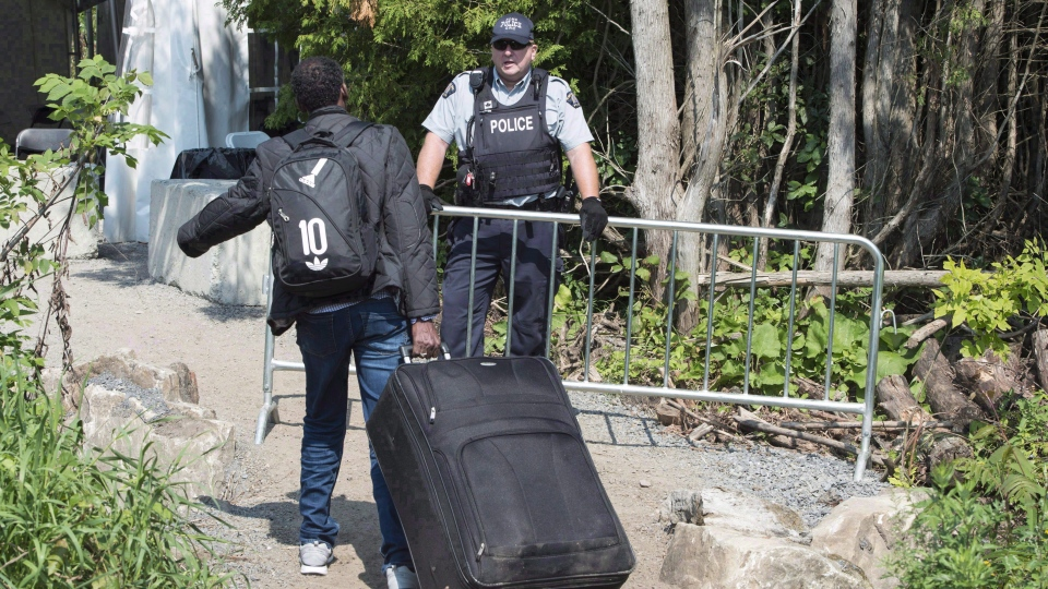 An asylum seeker, claiming to be from Eritrea, is confronted by an RCMP officer as he crosses the border into Canada from the United States on August 21, 2017 near Champlain, N.Y. (THE CANADIAN PRESS/Paul Chiasson)