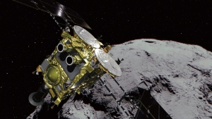 This computer graphics image provided by the Japan Aerospace Exploration Agency (JAXA) shows an asteroid and asteroid explorer Hayabusa2. (JAXA via AP)