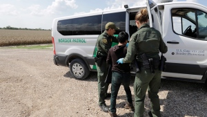 U.S. Border Patrol agents load a migrant from Guatemala into a van after he was caught trying to enter the United States illegally in Hidalgo, Texas on Monday, June 25, 2018. (AP Photo/David J. Phillip)