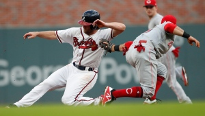 Atlanta Braves' Charlie Culberson, left, slides past the tag from Cincinnati Reds shortstop Jose Peraza to steal second base in the second inning of a baseball game Tuesday, June 26, 2018, in Atlanta. (AP Photo/John Bazemore)