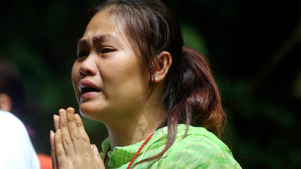One of relatives of 12 young soccer team members and their coach prays for their rescue after going missing in Tham Luang Nang Non cave, Wednesday, June 27, 2018, in Mae Sai, Chiang Rai province, northern Thailand. Rain is continuing to fall and water levels keep rising inside a cave in northern Thailand, frustrating the search for the boys and their soccer coach who have been missing since Saturday. (AP Photo/Sakchai Lalit)