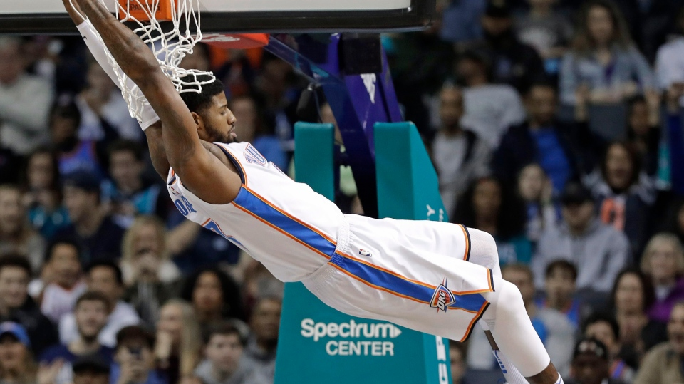 In this Jan. 13, 2018, file photo, Oklahoma City Thunder's Paul George (13) hangs from the rim after a dunk against the Charlotte Hornets during the first half of an NBA basketball game in Charlotte, N.C. (AP Photo/Chuck Burton, File)