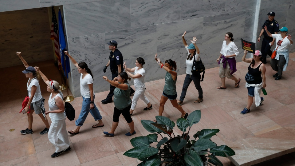 Protesters hold their hands up as they are escorted out of the Hart Senate Office Building after protesting the separation of immigrant families, Thursday, June 28, 2018, on Capitol Hill in Washington. (AP Photo / Jacquelyn Martin)