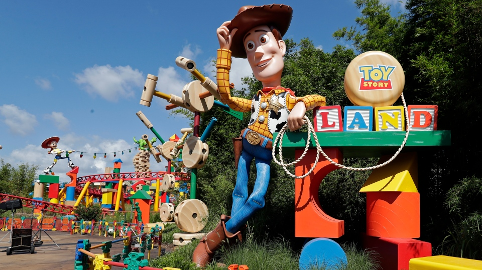 A statue of the character Sheriff Woody greets visitors at the entrance Toy Story Land in Lake Buena Vista, Fla. (AP Photo/John Raoux)
