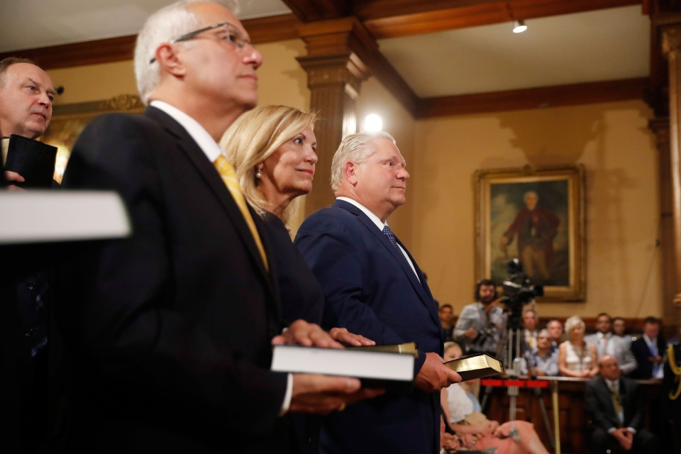 Doug Ford (right) is sworn in as premier of Ontario during a ceremony at Queen's Park in Toronto on Friday, June 29, 2018. Cabinet ministers Christine Elliott and Vic Fedeli look on. THE CANADIAN PRESS/Mark Blinch
