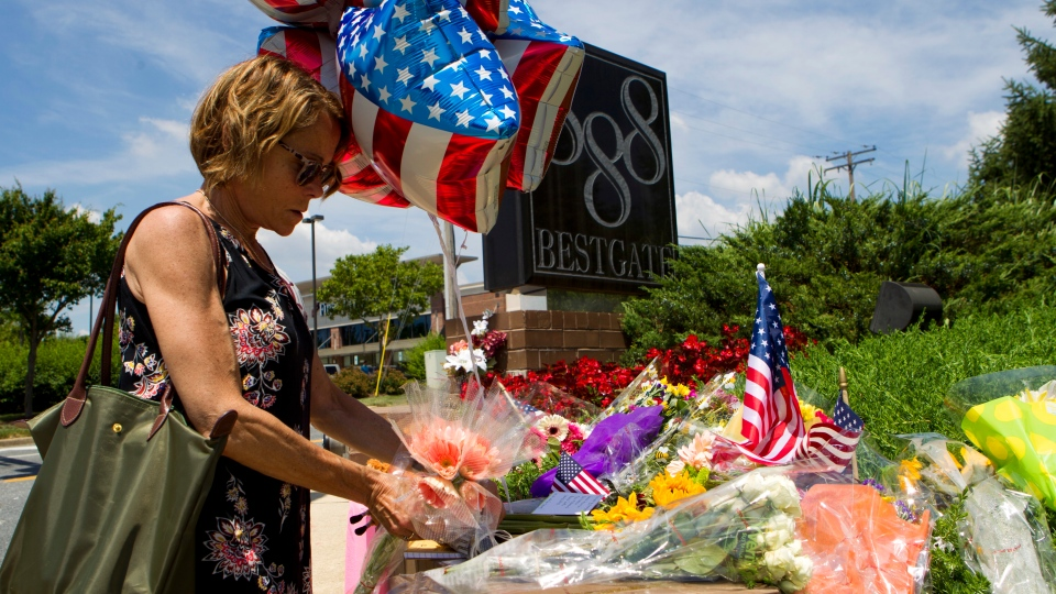 Neighbor Elly M. Tierney places flowers at a makeshift memorial at the scene outside the office building housing The Capital Gazette newspaper in Annapolis, Md., on Friday, June 29, 2018. (AP Photo/Jose Luis Magana)