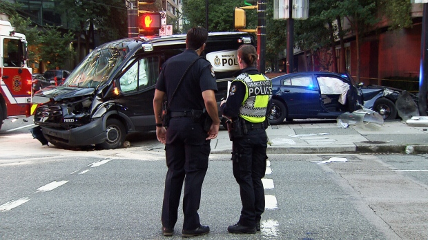 Police officers examine crash of VPD vehicles