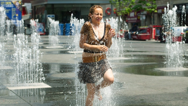 In this file photo, a woman cools down in the water sprinklers at Dundas Square as she take in the extreme heat in Toronto on Tuesday, June 19, 2012. (Nathan Denette / THE CANADIAN PRESS)