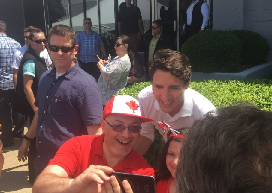 Prime Minister Justin Trudeau poses for a selfie with a man and child in Leamington, Ont. on Sunday, July 1, 2018. (Ricardo Veneza)