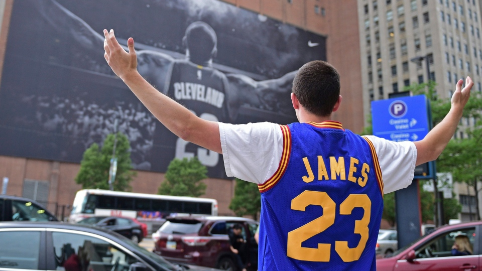 In this June 9, 2017, file photo, Cleveland Cavaliers fan Jordan Phillips poses for a photo in front of a poster featuring Cleveland Cavaliers forward LeBron James, before Game 4 of the basketball's NBA Finals between the Cavaliers and the Golden State Warriors, in Cleveland. (AP Photo/David Dermer, File)