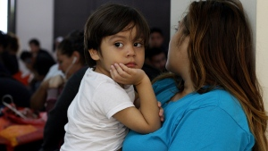 Katty Rodriguez and her 3-year-old son, Jose Luis, who were recently deported from the U.S. wait for their turn in La Chacra Immigration Center, in San Salvador, El Salvador, June 28, 2018. (AP / Salvador Melendez)