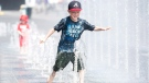 Seven-year-old Samuel Bedard from Quebec City runs through a water fountain as he beats the heat during a heatwave in Montreal, Monday, July 2, 2018. (THE CANADIAN PRESS/Graham Hughes)
