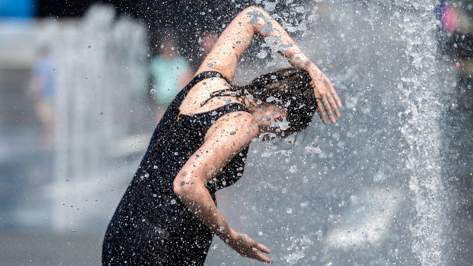 A woman cools down in a water fountain as she beats the heat in Montreal, Monday, July 2, 2018. (THE CANADIAN PRESS/Graham Hughes)