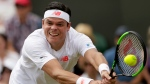 Milos Raonic of Canada returns the ball to John Millman of Australia during their men's singles match on the third day at the Wimbledon Tennis Championships in London, Wednesday July 4, 2018. (AP Photo/Tim Ireland)